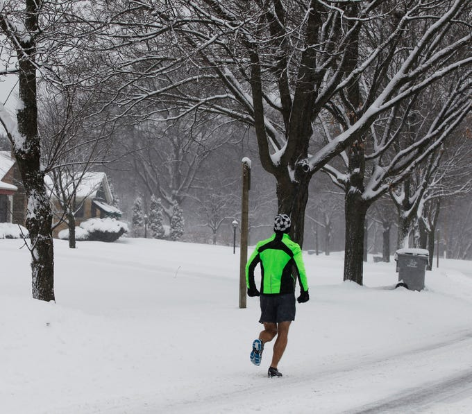 A dedicated runner, doesn't seem to be phased by the falling snow while running in shorts along Menomonee River Parkway in Wauwatosa.