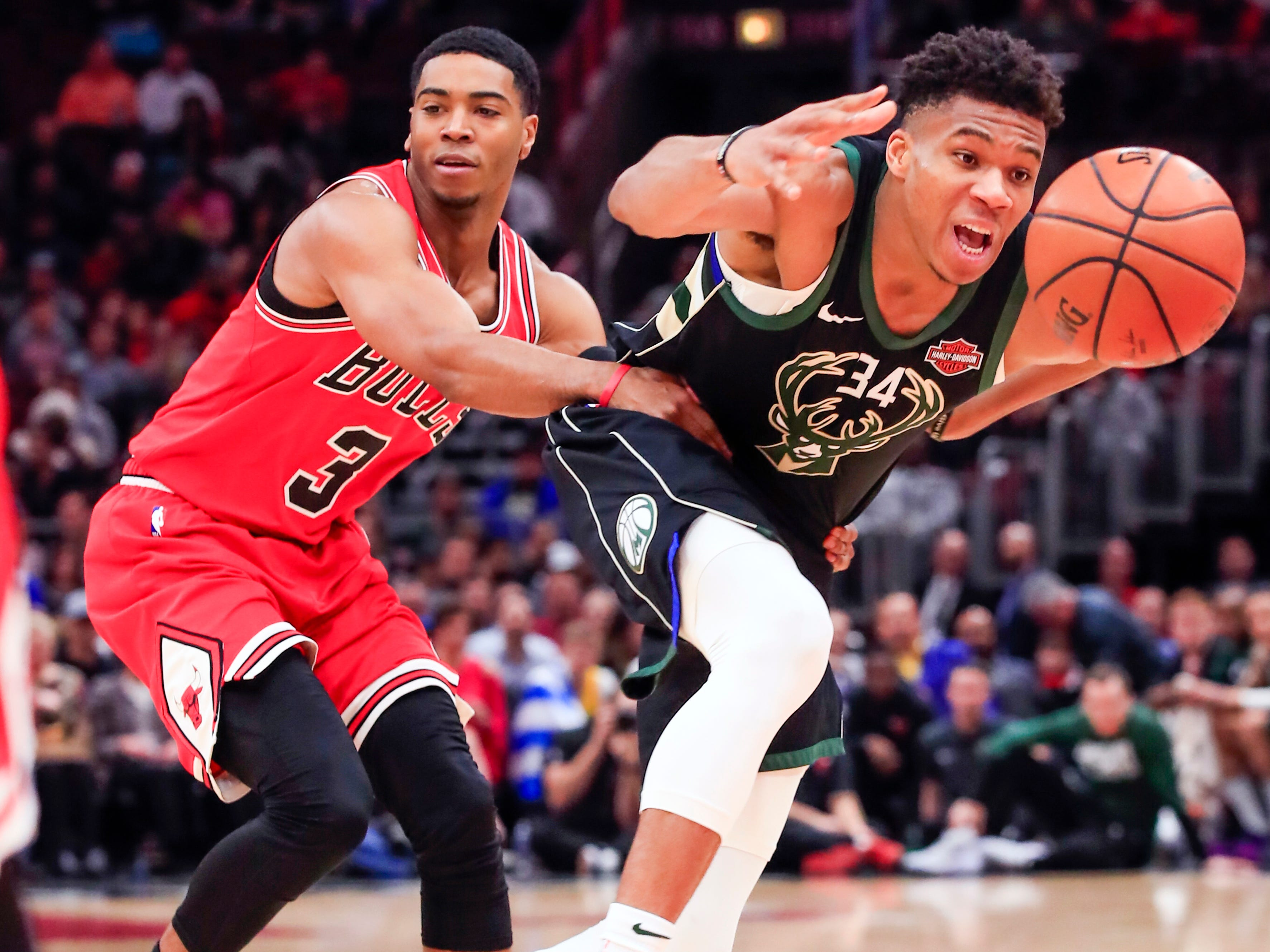 Bulls guard Shaquille Harrison grabs a hold of Giannis Antetokounmpo by the waist to make the Bucks forward doesn't doing any damage on a fast break during the first half Monday.