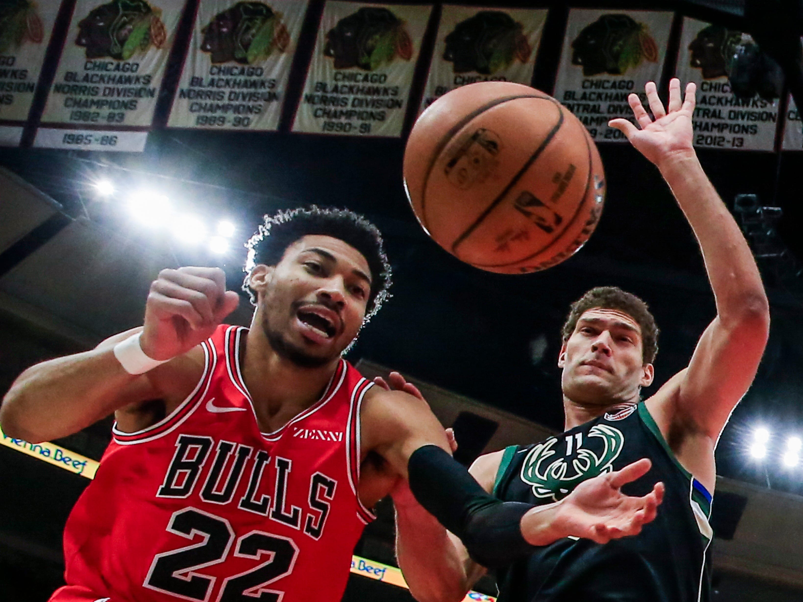 Otto Porter Jr. of the Bulls scrambles to get to the ball before it goes out of bounds as Bucks center Brook Lopez looks on Monday night.
