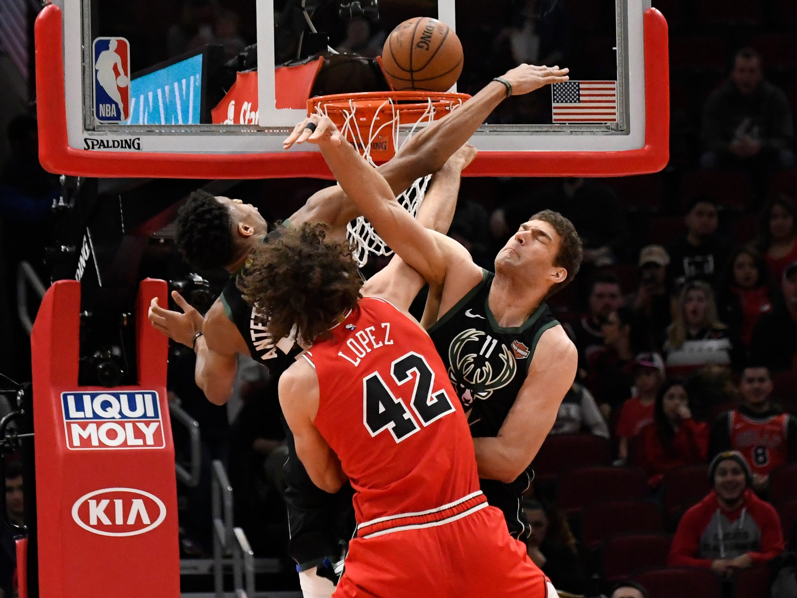 Bucks center Brook Lopez (right) blocks the shot of Bulls center Robin Lopez, his twin brother, as Giannis Antetokounmpo lends support during the first half Monday.