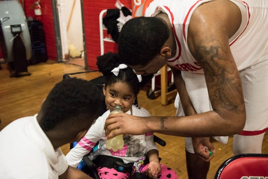 Lee's Demond Robinson helps his sister, Geonni Johnson, 4, get a sip of lemonade during his game at Lee High School in Montgomery, Ala., on Tuesday, Feb. 5, 2019. Geonni was diagnosed with Acute flaccid myelitis a nervous system disease after she fell ill last year.