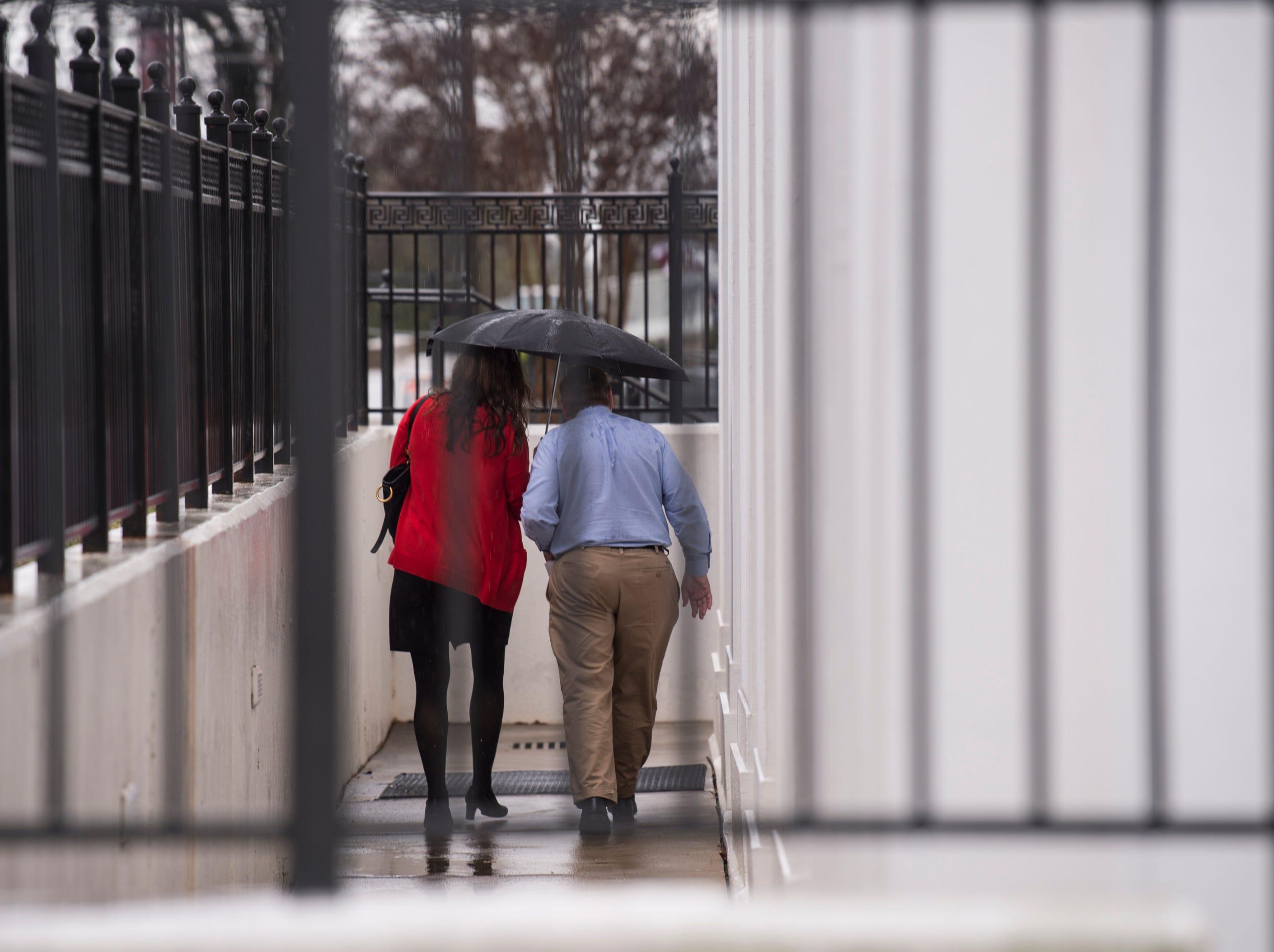 Pedestrians share an umbrella in Montgomery, Ala., on Tuesday, Feb. 12, 2019.