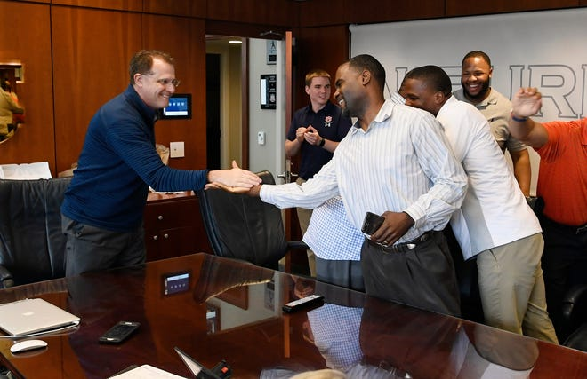 Auburn head coach Gus Malzahn (left) high fives assistant Marcus Woodson (right) after Charles Moore announces he's signing with Auburn on National Signing Day on Wednesday, Feb. 6, 2019 in Auburn, Ala.