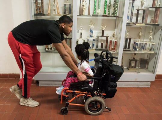 Demond Robinson pushes his sister Geonni Johnson, 4, down the hallway after his game in Montgomery, Ala., on Tuesday, Feb. 5, 2019. Geonni was diagnosed with Acute flaccid myelitis a nervous system disease after she fell ill last year.