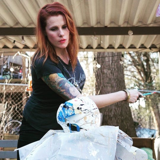 Artist Jessica Fife poses as she paints the shaping helmet she helped decorate for the Wright family.