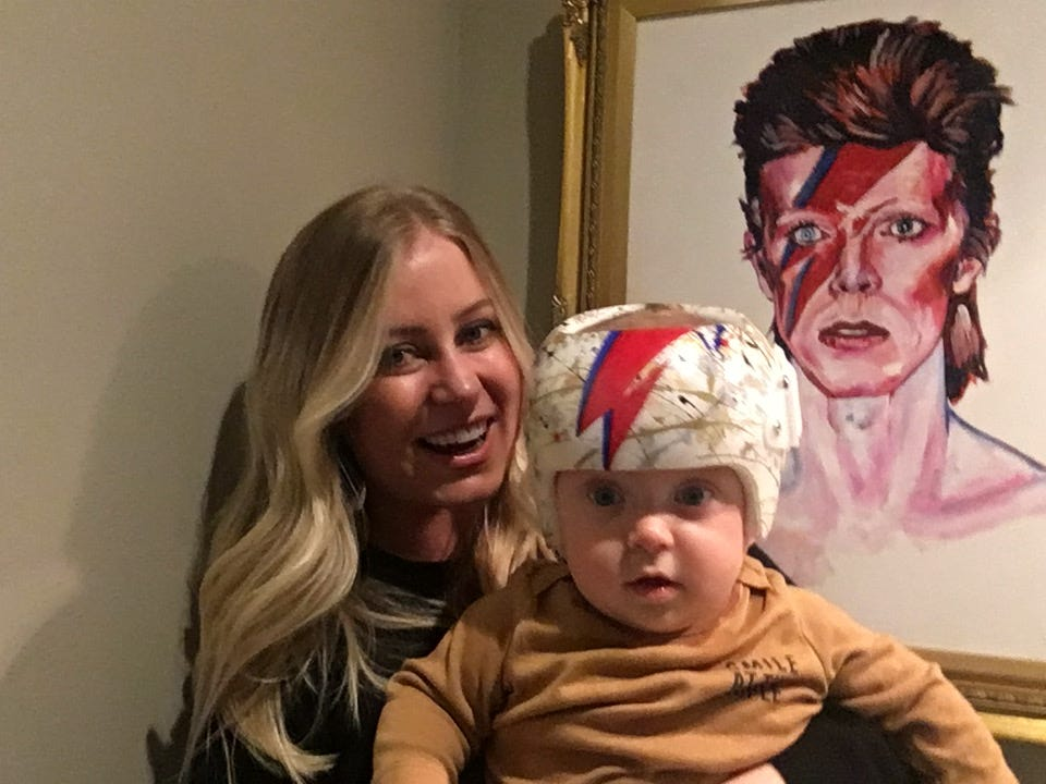 Jillian and Arden Wright pose in front of a portrait of David Bowie in their home. The painting was part of the inspiration for the paint job on Arden's new shaping helmet, done by East Nashville artist Jillian Wright.