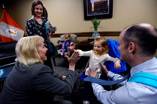 Claire Fox, 4, high fives Tennessee State Sen. Becky Duncan Massy, R-Knoxville, before her parents, Jessica, left, and Sean talk with her during Disability Day on the Hill Tuesday, Feb. 12, 2019, in Nashville, Tenn. Families and advocates of people with disabilities in Tennessee met with lawmakers to express concerns and the needs of the disabled in the state.