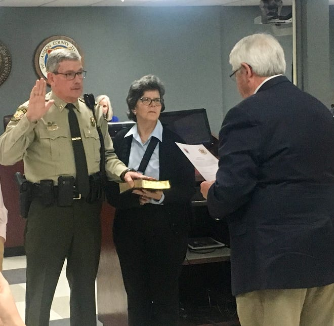 Dusty Rhoades, standing next to his wife, Lynn, is sworn in as the new Williamson County Sheriff on Monday, Feb. 11, 2019.