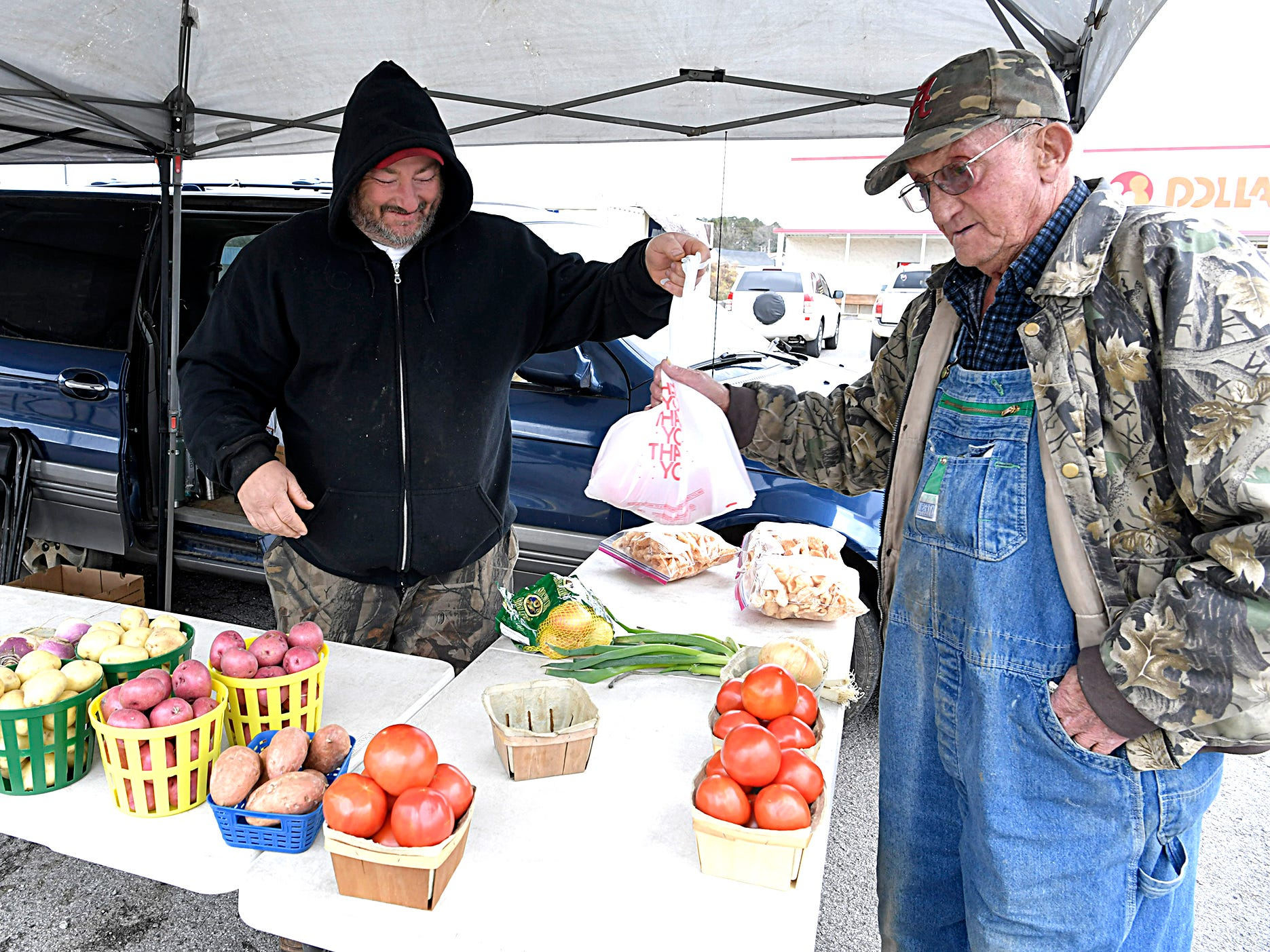 Kent Kisselburg sells vegetables to Lee Chambers at Kisselburg's stand in parking lot in Ducktown, Tennessee on Dec. 4, 2018.