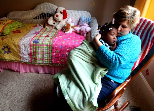 Barb Jones rocks her daughter, Dara, 4, at their Franklin home in February 2010. The family will celebrate Dara's 13th birthday on Valentine's Day.