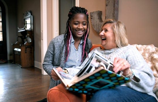 Dara Jones, 12, and her mother, Barb Jones, look at photographs of Dara when she first arrived to the United States in 2010 after the Haiti earthquake.