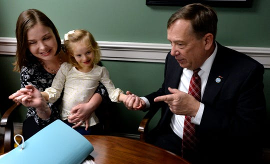 Claire Fox, 4, who has Cri du chat, a chromosomal deficiency, holds the hand of state Rep. Sam Whitson as her mother, Jessica, talks with him during Disability Day on the Hill on Tuesday, Feb. 12, 2019, in Nashville.