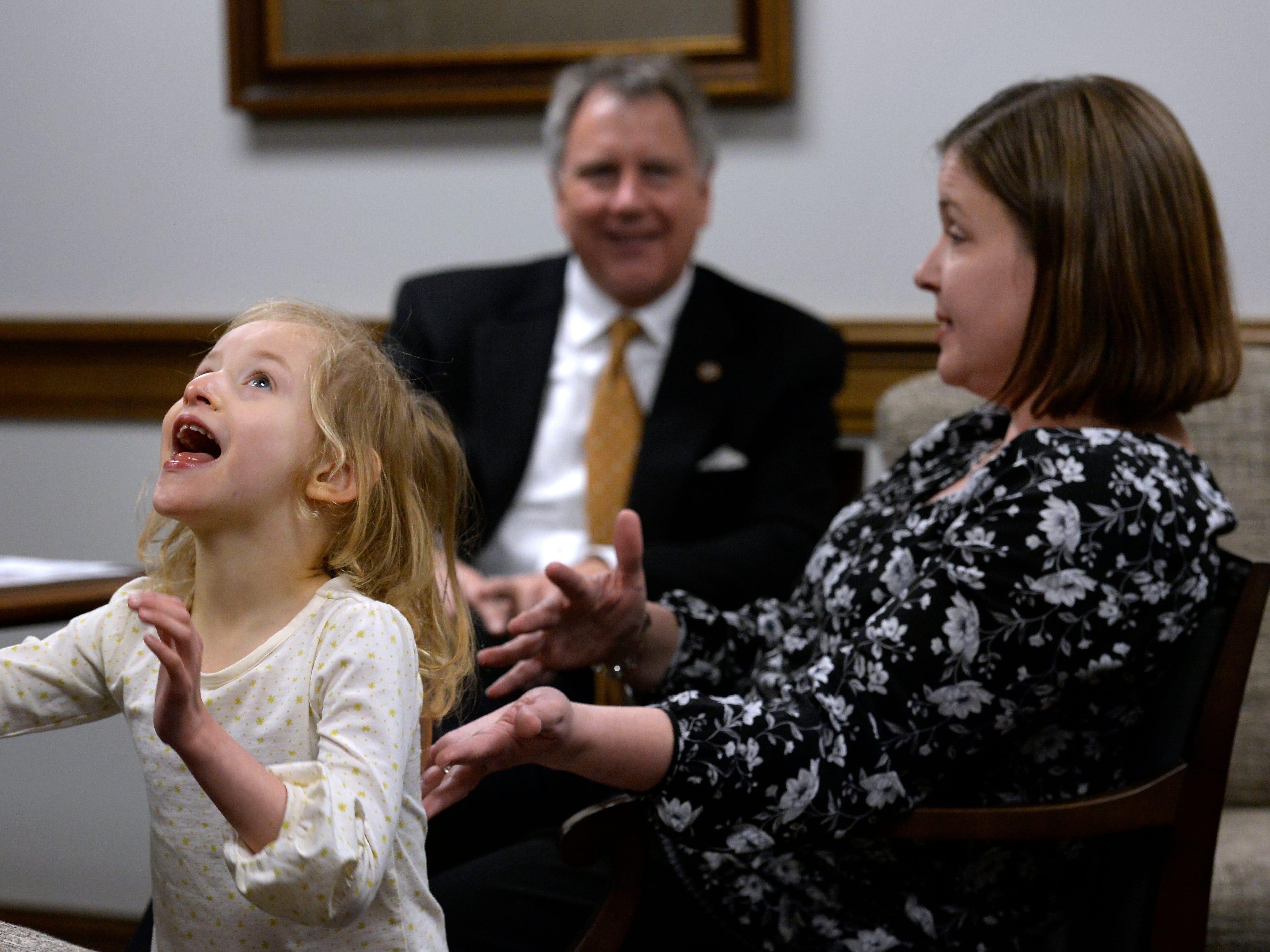 Jessica Fox talks with state Sen. Kerry Roberts as her daughter Claire, 4, who has Cri du chat, a chromosomal deficiency, plays in his office during Disability Day on the Hill on Tuesday, Feb. 12, 2019, in Nashville.