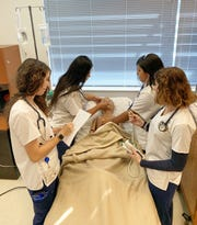 "Nursing students (from left) Makenna Gorman, Emely Diaz, Kaitlyn Flores and Riley Mulhern practice assessing and admitting ""Pedi,"" their 5-year-old high fidelity pediatric simulator in the Lorenzo Walker Technical College Simulation Lab."
