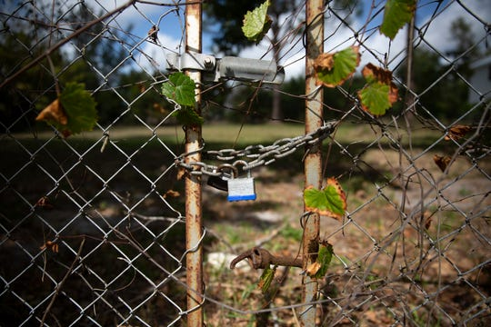A lock on a fence keeps the gates closed on a Collier County-owned property, Tuesday, Feb. 12, 2019, at the corner of Bayshore and Jeepers Drive in East Naples. Florida Gulf Coast University is proposing to put a water quality research center at the site.