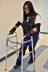 Nursing student Emely Diaz is wearing a geriatric simulation suit. The weighted vest simulates the aging process by shifting the center of gravity down. Neck, elbow, wrist and knee braces reduce the range of motion in the joints. The ankle weights simulate how heavy the legs can feel when we age. The glasses simulate cataracts and reduced visual acuity.