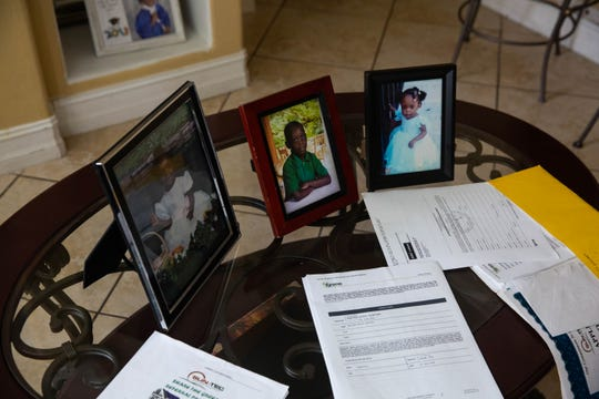 The contracts Marceau Berteau says he was misled into signing sit on a table with photos of his three children in Golden Gate on Feb. 12, 2019. Because of solar panels Berteau says he was misled to install, his family is having financial struggles and are afraid of losing their home, which was built six years ago by Habitat for Humanity.
