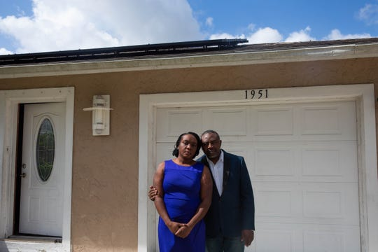 """Maltide and Marceau Berteau stand outside their home in Golden Gate on Feb. 12, 2019. The Berteaus have lived in their Habitat for Humanity home for six years and installed solar panels in June 2018 through the PACE program by a contractor Marceau Berteau said told him that the panels would be free and would reduce his cost of living. Instead, the loan for the panels potentially will cost the Berteaus over $40,000. Since he cannot work due to complications with his health, Maltide Berteau is the sole provider for the family. """"I accepted it because life is not easy,"""" he said. """"But now I am afraid we will lose our house."""""""