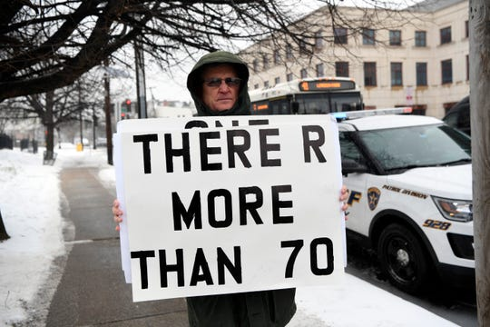 "Robert Hoatson, co-founder and president of Road to Recovery, holds a sign reading ""there are more than 70"" in reference to sexual abuse cases against New Jersey priests, as the Archdiocese of Newark holds a meeting regarding this list of abusive priests on Tuesday, Feb. 12, 2019."