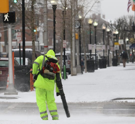 Derek Newman with the Morristown Department of Public Works blows snow off the sidewalk before it ices up on West Park Place on February 12, 2109.