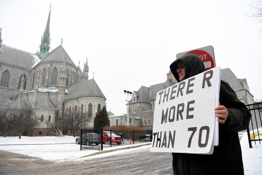 """Robert Hoatson, co-founder and president of Road to Recovery, holds a sign reading, """"there are more than 70,"""" as priests leave a meeting at the Archdiocese of Newark regarding a list of sexually abusive priests on Tuesday, Feb. 12, 2019."""