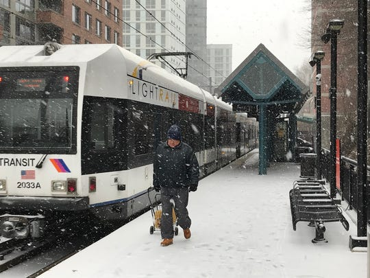 A man walks at the 9th Street Hudson Light Rail station in Hoboken as a snow storm hits the area on Feb. 12, 2019.