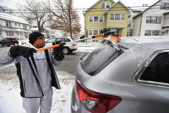 Paterson resident Elliston Sample removes snow from his car   in Paterson on 02/12/19.