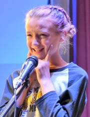 """Fifth-grader Arden McWhorter, 11, of Chaparral Elementary scrunches her face in attempt to spell the word, """"clique."""""""