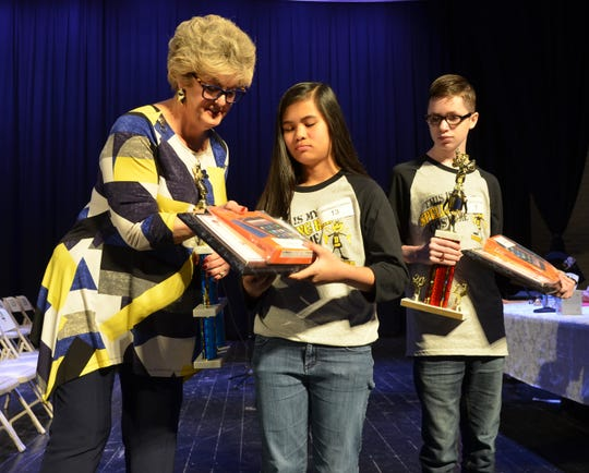 Pronouncer Suzanne Lundy presents a trophy and some gifts to first place Deming Public Schools Spelling Bee winner Franchesca Coloma of Red Mountain Middle School. At right, runner-up Angelo Granado also of Red Mountain Middle School.