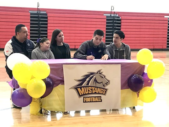 Deming High Wildcat quarterback Daniel Garcia signed on to play football at Western New Mexico University on Monday with family looking on.
