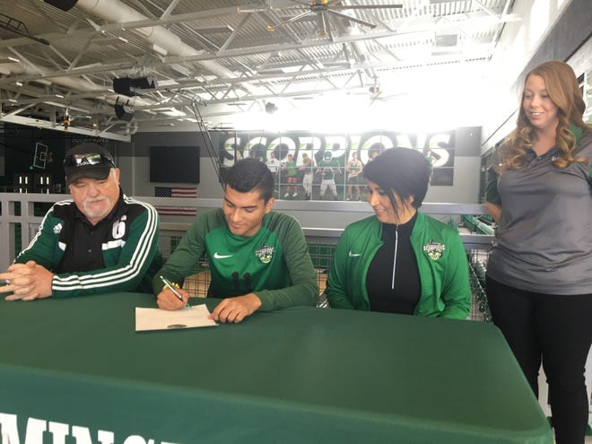 Farmington's Brandon Zamudio signs his letter of intent on Tuesday to continue his soccer career at Feather River College in Quincy, California.