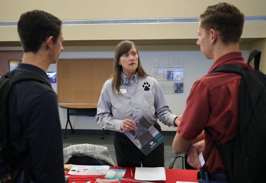 From left, San Juan College students Anthony Bernardone and Marcelino Bernardone talk with Catherine Walker Grobler, an enrollment success coach, about academic programs at the University of New Mexico.