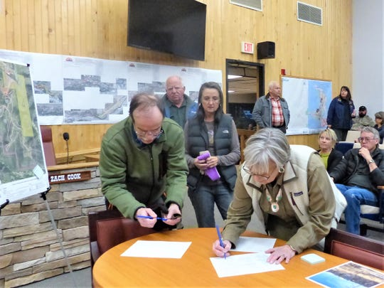 People signing in for the meeting included Frederick Moras, a cycling enthusiast, and Laura Doth, with Southcentral Mountain Resource Development and Conservation District.