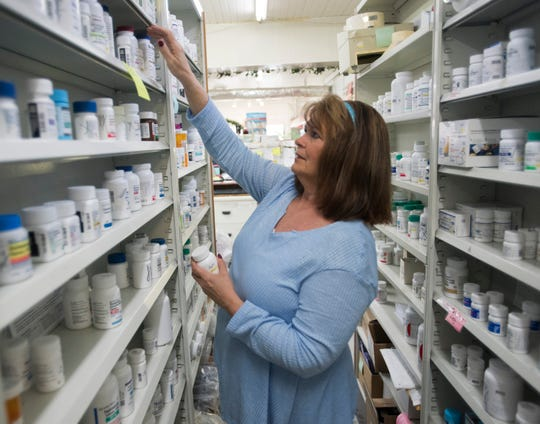Julie Booth-Moran, the owner of Century Pharmacy, in Century, Fla. searches for medications from inventor to fill a prescription on Monday, Feb. 11, 2019. The small independent pharmacy has operated in the town of Century since 1900. Booth-Morna has worked at the drug store since the late 1970s