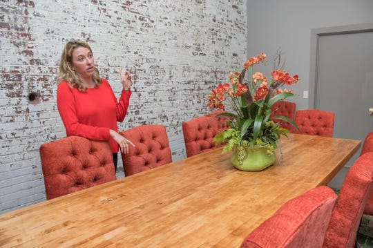 Owner McKenzie Lovelace talks about the old butcher block from the Premier Baking Company that now serves as the table in the private dining room at the Cypress restaurant in Pensacola on Tuesday, February 12, 2019.