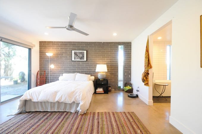 The master suite features a bare concrete wall and complementary vertical, rectangular windows.