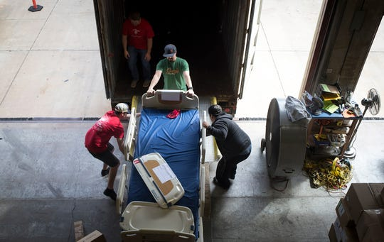 Volunteers load a hospital bed into a shipping container, January 30, 2019, at Project C.U.R.E., 2100 W 14th St., Tempe.