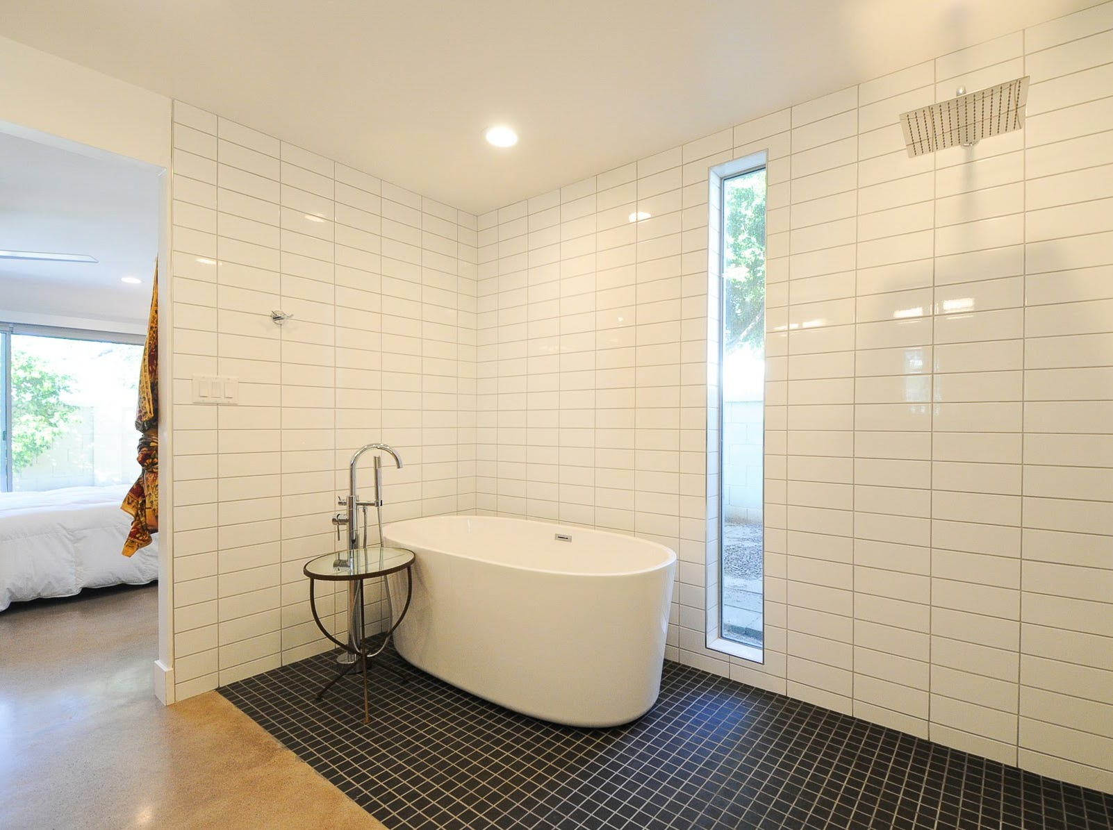 The master bath features a uniquely open shower suite, with a sleek soaking tub and a square, rainfall shower head.