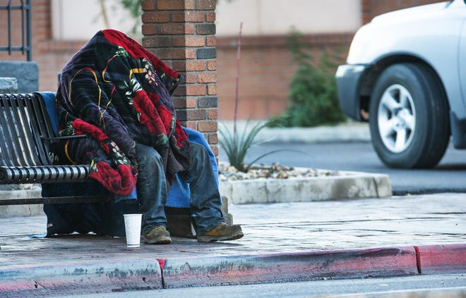 A man waits bundled up at a bus stop on Mill Avenue near University Boulevard in Tempe Jan. 2, 2019.