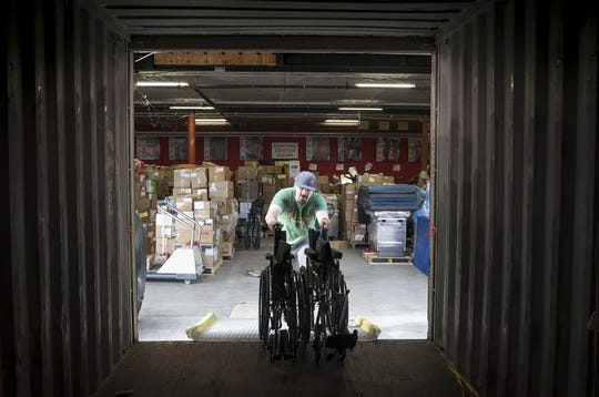 Volunteer Cameron Long loads wheelchairs into a shipping container, January 30, 2019, at Project C.U.R.E., 2100 W 14th St., Tempe.