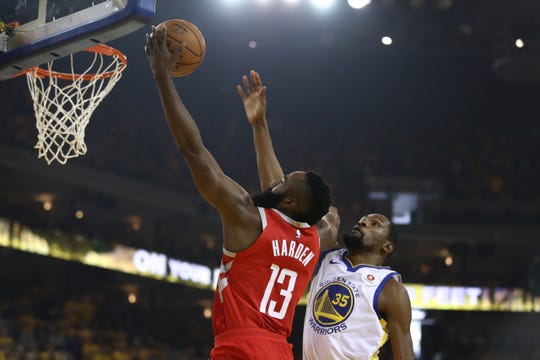 James Harden intenta encestar la bola ante el acoso de Kevin Durant de los Warriors.