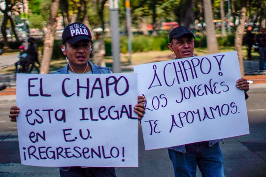 Dos hombres sostienen carteles con mensajes de apoyo a 'El Chapo' Guzmán, afuera de la corte.