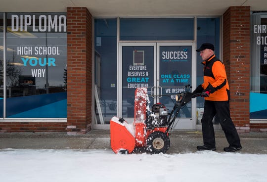 Mike Glombowski, owner of Mike Glombowski Snow Handling, uses a snowblower to clear a sidewalk Tuesday, Feb. 12, 2019 in downtown Port Huron.