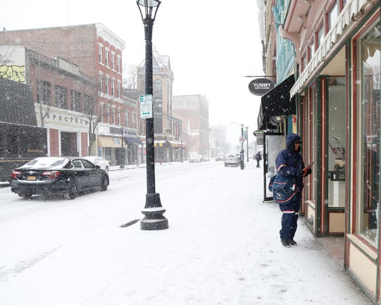 Lisa Andino, letter carrier for the United States Postal Service, delivers mail on Main Street in Poughkeepsie, New York, on Feb. 12, 2019.