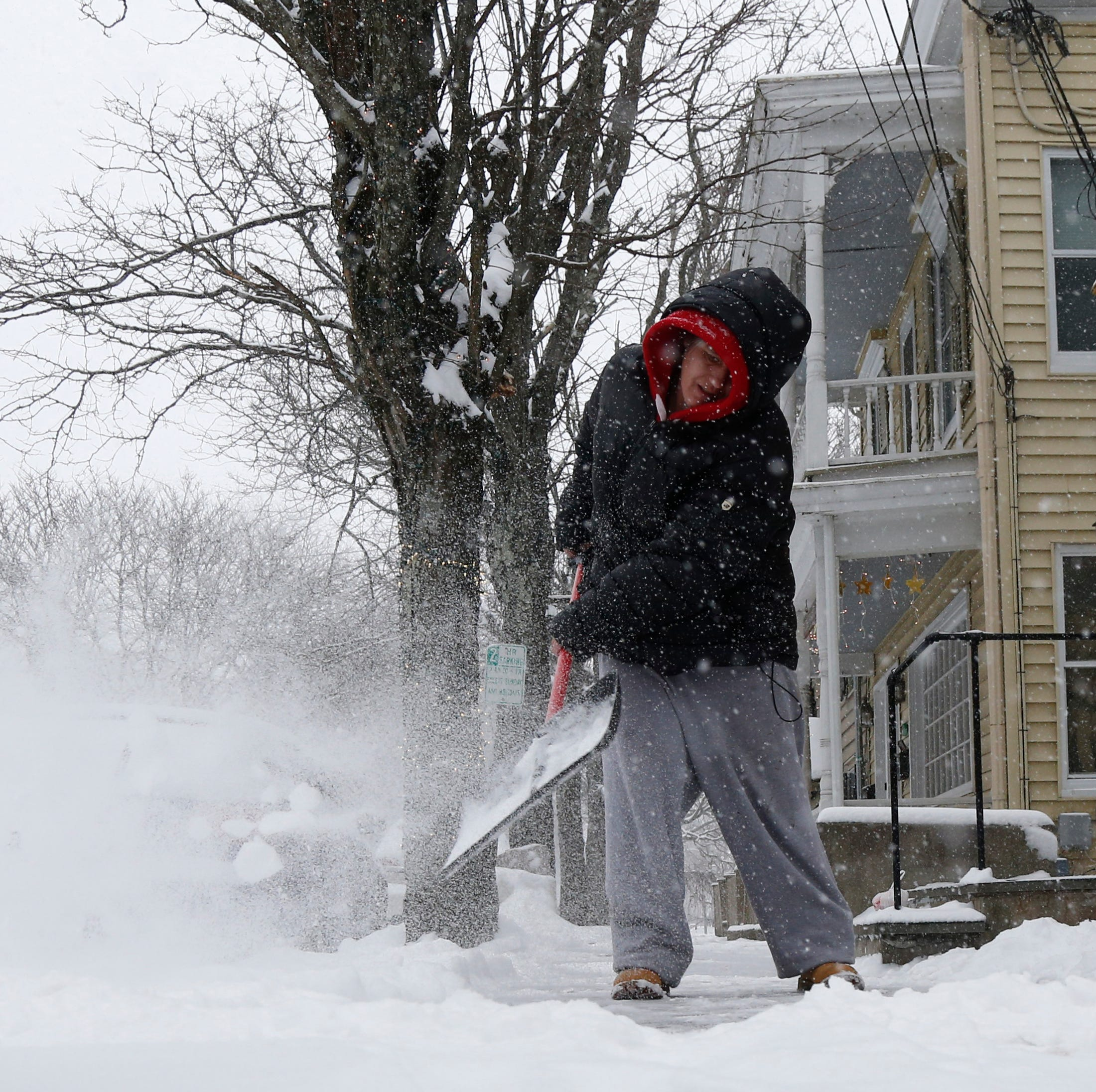 Idania Williams shovels the snow in front of her neighbor's restaurant on Market Street in Rhinebeck on February 12, 2019.