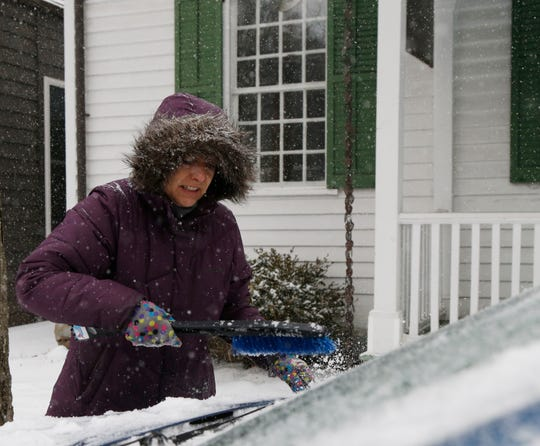 Sue Grace brushes the snow off of her car after having lunch in Rhinebeck on February 12, 2019.