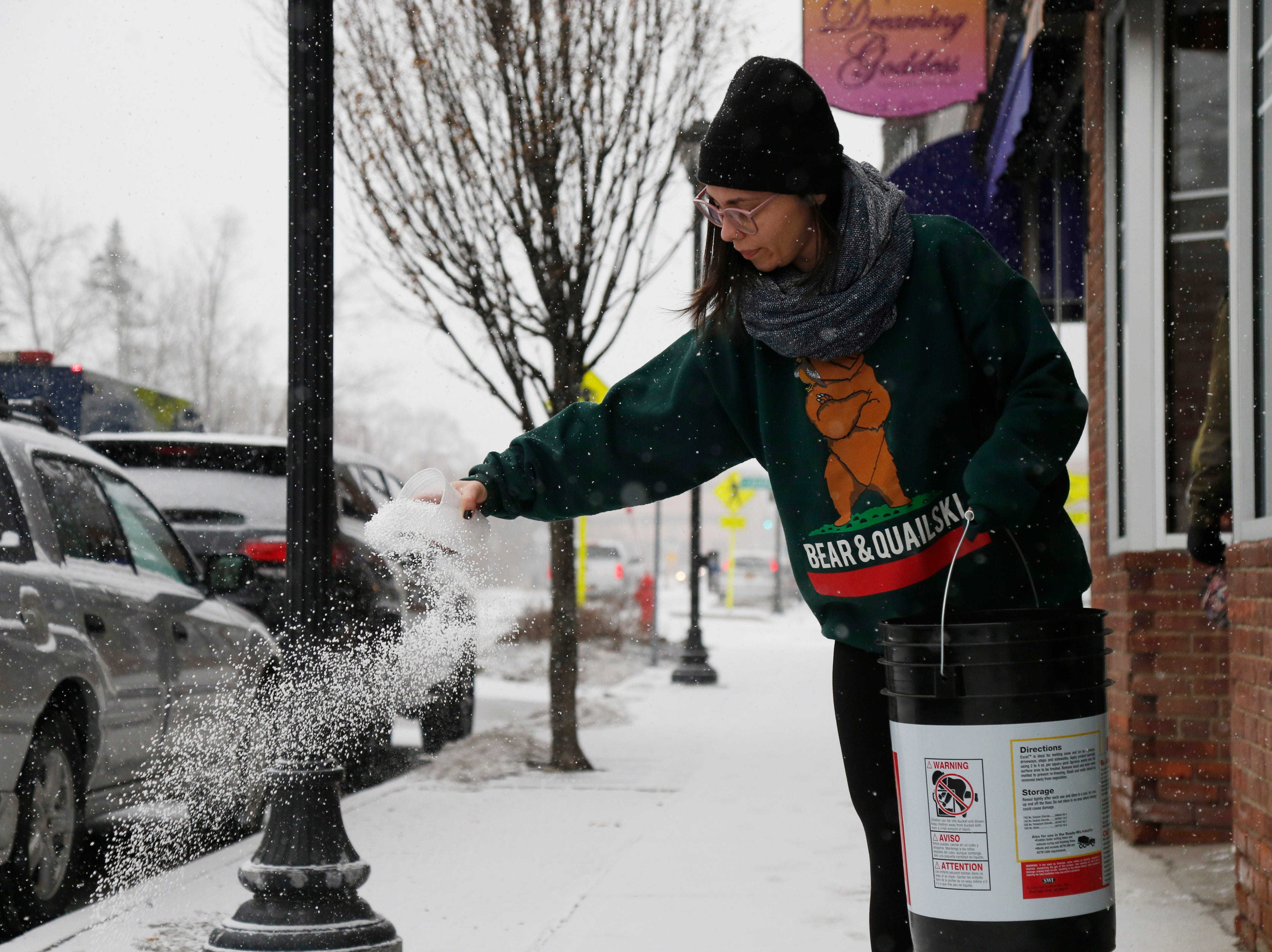 Angela Hernandez spreads ice melter to the sidewalk outside the Crafted Kup in the Arlington Business District of the Town of Poughkeepsie on February 12, 2019.
