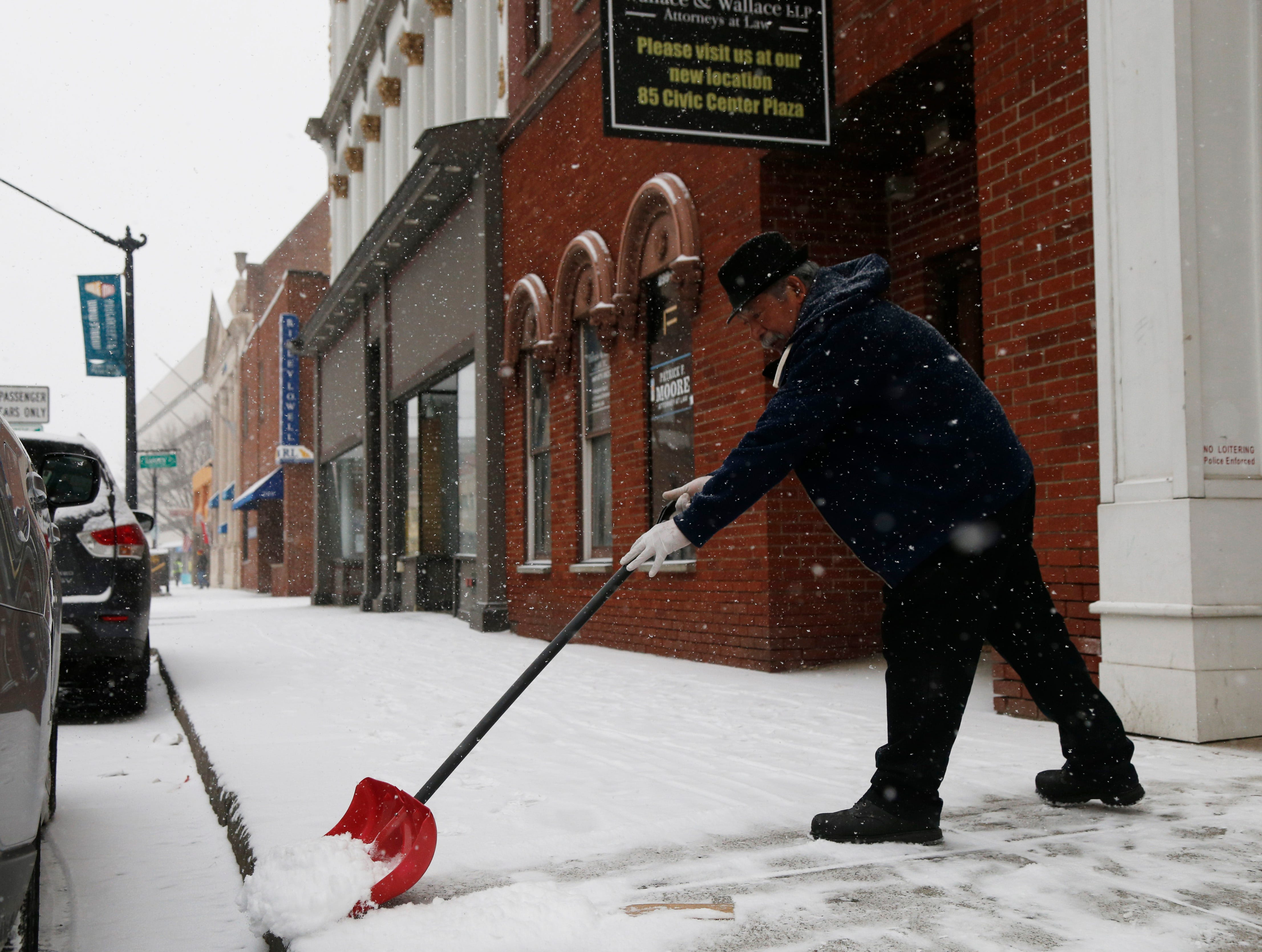 Eddie Jimenez clears snow from the sidewalk outside The Artist's Pallate in the City of Poughkeepsie on February 12, 2019.