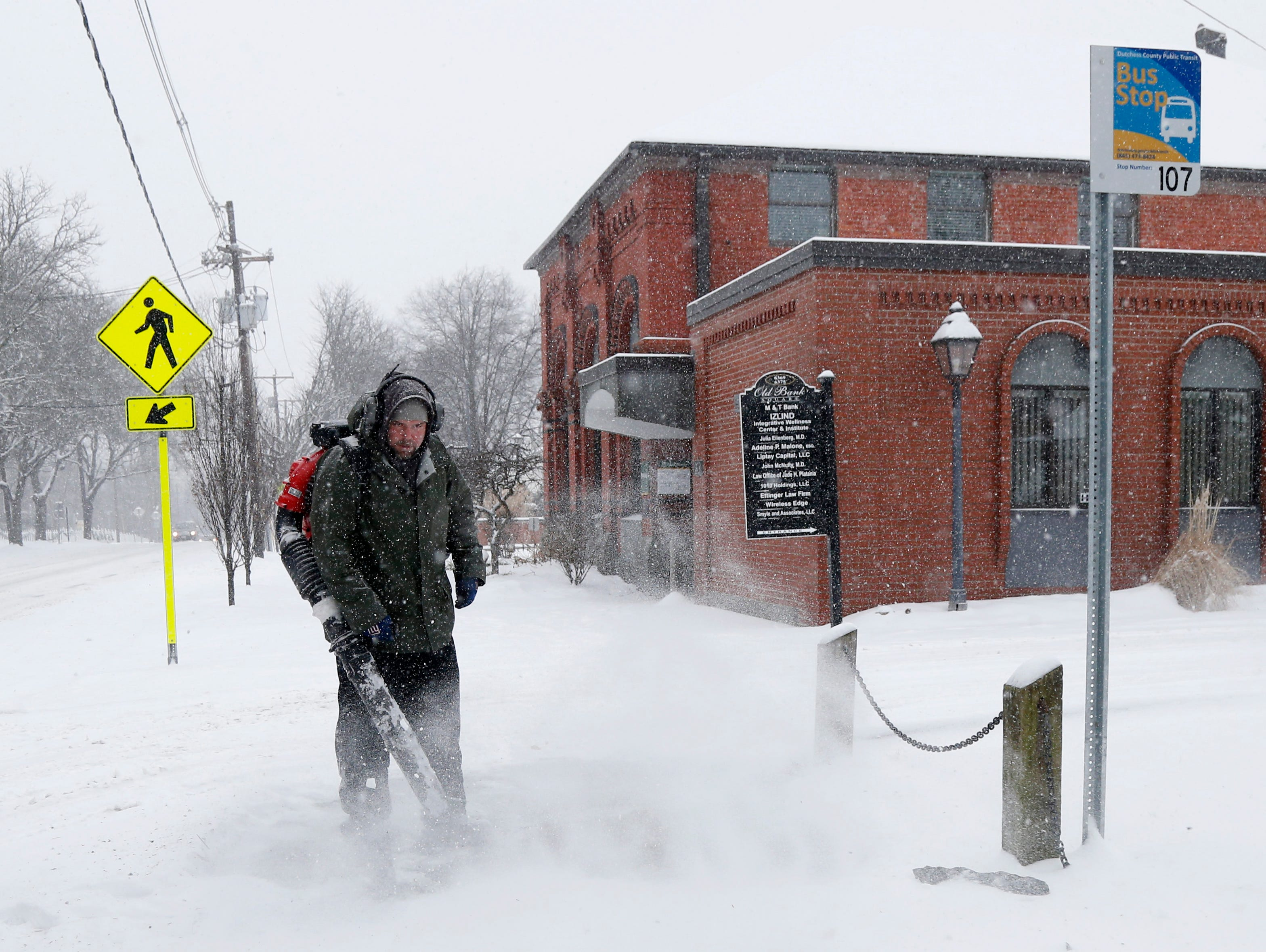 Casey Martin, a contractor for the USPS uses a leaf blower to clear snow from the sidewalk in front of the Rhinebeck Post Office on Mill Street on February 12, 2019.
