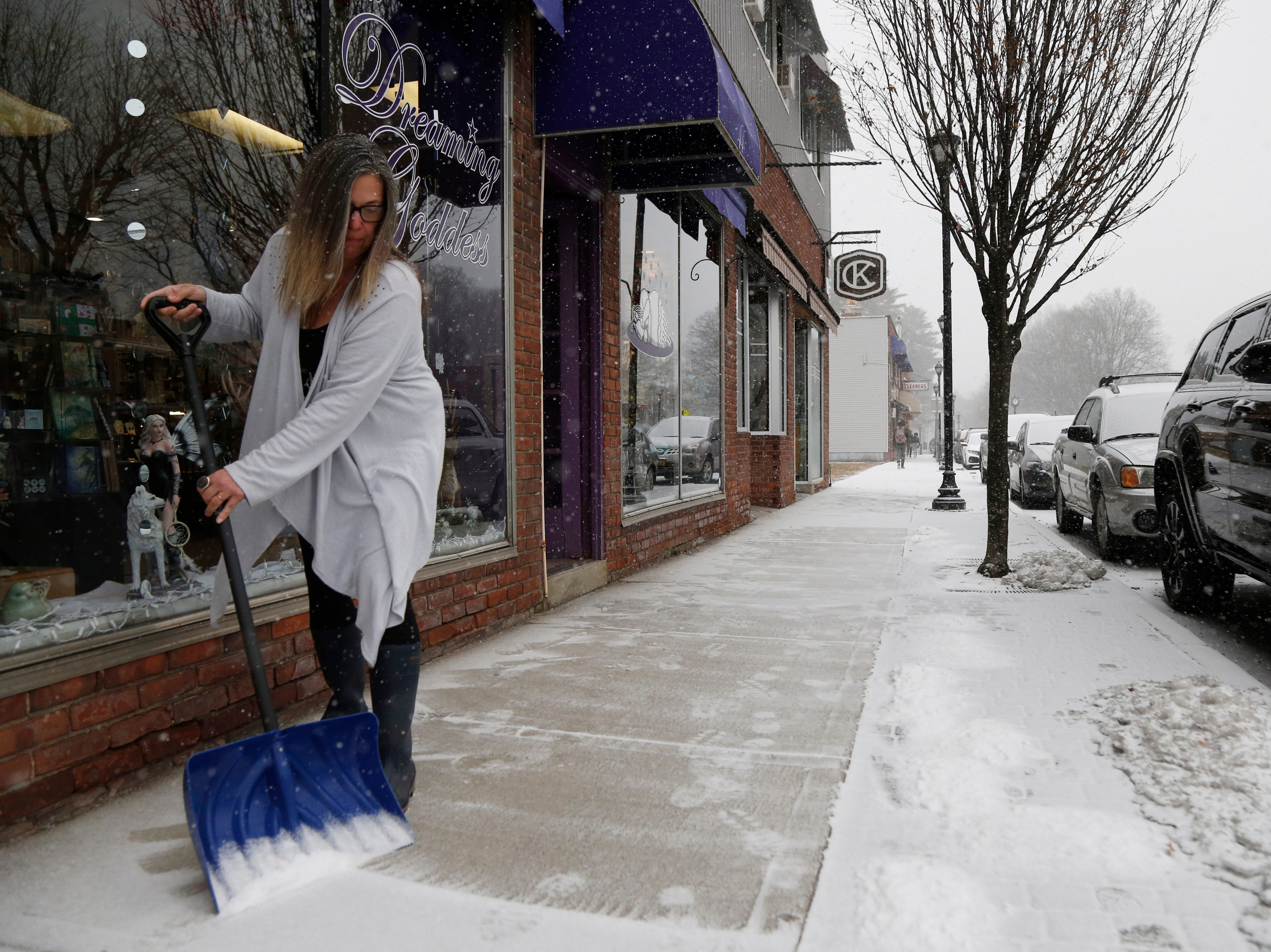 Shayleen Kutz clears snow from the sidewalk outside the Dreaming Goddess in the Arlington Business District of the Town of Poughkeepsie on February 12, 2019.